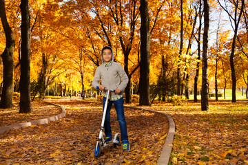 Boy ride scooter in October park