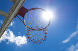Dark basketball hoop and net against the sun