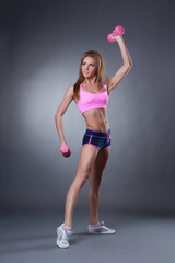 Muscular young woman exercising with dumbbells