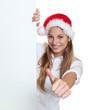Frau mit Nikolausmütze zeigt Daumen hinter Werbetafel