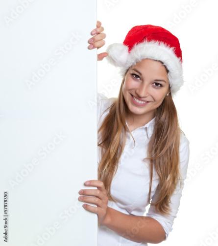 Frau mit Nikolausmütze schaut hinter Werbetafel hervor