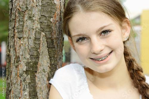 Teenager mit Zopf lehnt an Baum
