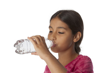 Young teenage girl drinking fresh water from a bottle