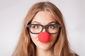 Close-up portrait of a happy 20s girl with red clown nose