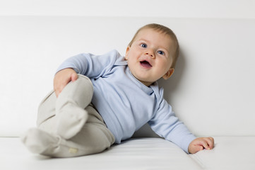 Portrait of cute smiling baby boy lying on sofa.