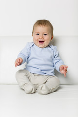 Portrait of sweet overjoyed baby boy sitting on sofa.