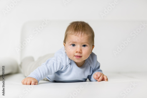 Portrait of cute baby boy lying on belly.