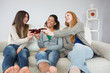 Cheerful female friends toasting wine glasses at home