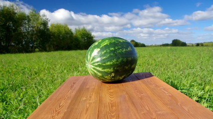 Watermelon on a wooden table.Background blue sky