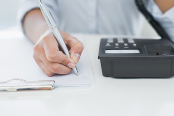 Mid section of woman using telephone while writing on clipboard