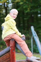 Active laughing teenager boy plays outdoors at playground