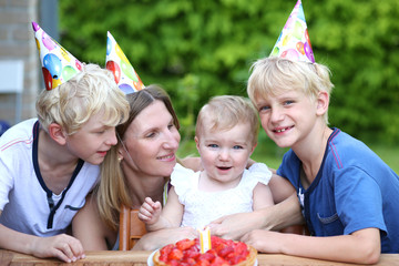 Mother and kids celebrating birthday of one year old baby girl