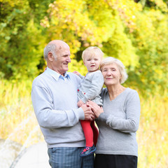 Happy grandparents with little baby granddaughter in the park