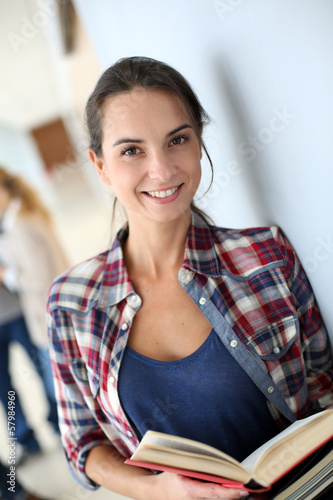 Smiling student girl standing in hall
