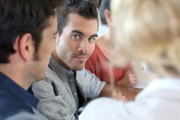 Portrait of young man attending meeting