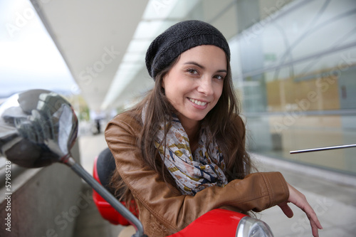 Attractive young woman sitting on red scooter