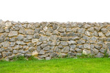 Fototapety fence real stone wall surface with cement on green grass field