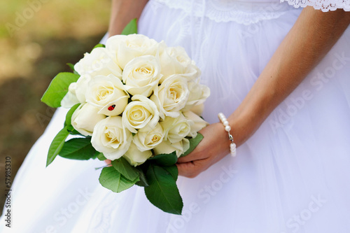 Wedding bouquet of white roses in hand of bride