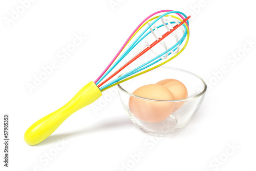 whisk on a glass bowl with eggs