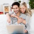 glückliches paar schaut auf laptop