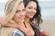Close up of two women covered with blanket at beach