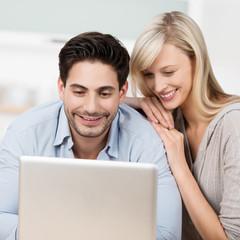 glückliches paar in der küche schaut auf laptop