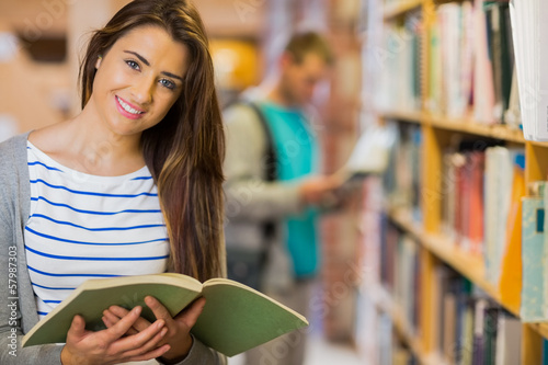 Two students by bookshelf in the library