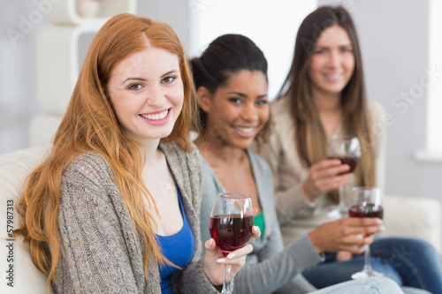 Smiling female friends with wine glasses at home