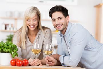 glückliches paar trinkt ein glas wein in der küche