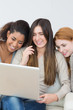 Cheerful female friends using laptop together on sofa