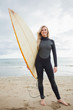 Smiling young woman in wet suit holding surfboard at beach