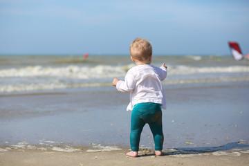 Cute blond baby girl in white blouse is walking along beach