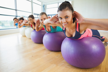 Portrait of class exercising on fitness balls in row