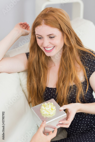 Beautiful young blond receiving a gift box on sofa