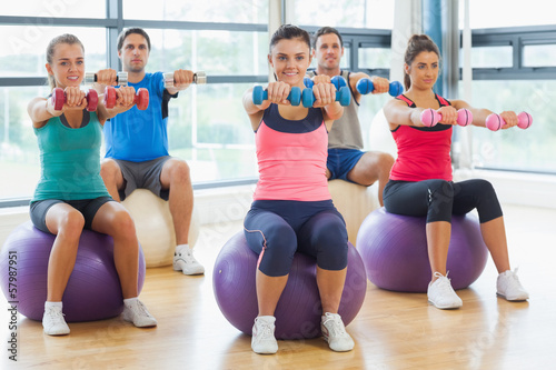 Fitness class sitting with dumbbells on exercise balls