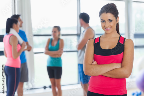 Instructor with fitness class in background in fitness studio