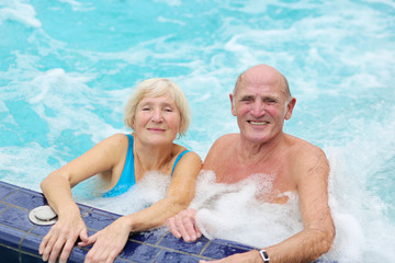 senior couple having fun together in the swimming pool jacuzzi