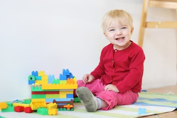 Funny baby girl playing indoors with colorful blocks