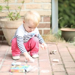 Cute little blond baby girl plays outdoors drawing with chalk