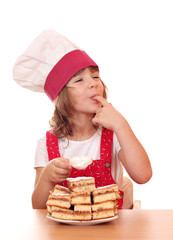little girl cook eat sugar from apple cake