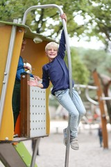 Active teenager boy having fun on playground in the park