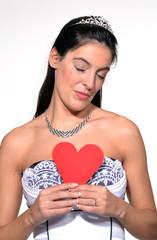 Novia enamorada sujetando un corazón de papel.