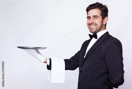 Handsome waiter holding an empty silver tray over gray backgroun