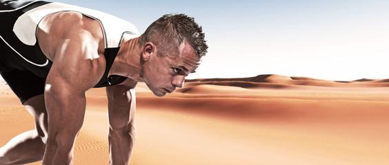 Extreme athlete runner man in starting position outdoor in deser