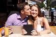 Девушка с парнем в кафе с планшетами