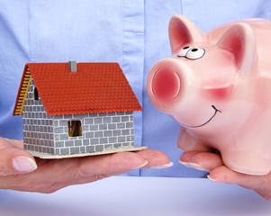 Bausparen - Frau mit Haus und Sparschwein