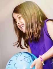 Portrait of very cute girl playing with a blue balloon