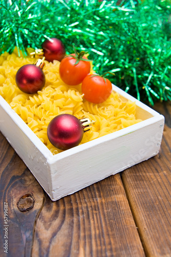 Cherry tomatoes, pasta, Christmas balls and  tinsel