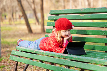 little girl learning with tablet pc in the park.