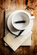 Cup of coffee with grunge notepad and pen on white tablecloth ba